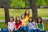 Insegnante madre con gli alunni della figlia in un parco giochi per — Foto Stock