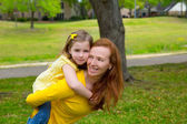 Daughter and mother piggyback smiling in park outdoor — Stock Photo