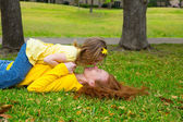 Daughter and mother playing lying on park lawn — Stock Photo