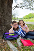 Sister firends girls relaxed under tree park after school — Stock Photo