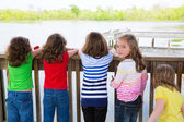 Children girls back looking at lake on railing — Stok fotoğraf