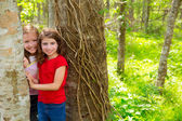 Children friends playing in tree trunks at the jungle park — Stock Photo