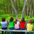 Children sister and friend girls sitting on forest park bench — Stock Photo