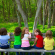 Children sister and friend girls sitting on forest park bench - Stok fotoğraf