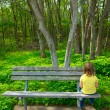Lonely children sad looking the forest sitting on bench  — Stock Photo