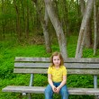 Stock Photo: Lonely children girl happy sitting on park bench