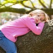 Children kid girl resting lying on a tree branch — Stock Photo