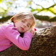 Blond children kid girl having a nap lying on a tree — Stock Photo #26180709