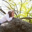 Beautiful children kid girl resting lying on a tree — Stock Photo #26180759