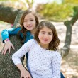 Friend sister girls resting on tree trunk nature — Stok fotoğraf