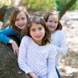 Friend sister girls resting on tree trunk nature - Stock Photo