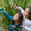 Sister twin girls playing in nature pointing finger — Stock Photo