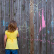Blonk kid girl playing with drawing chalks in the backyard — Stock Photo