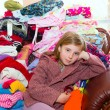 Blond kid girl sitting on a messy clothes sofa — Stock Photo