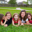 Children girls group lying on lawn grass smiling happy — Stock Photo