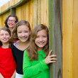 Grils group in a row smiling in a wooden fence — Stock Photo