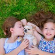 Stock Photo: Twin sisters playing with chihuahudog lying on lawn