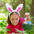 Easter girl with eggs basket and funny bunny face — Stock Photo