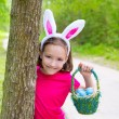 Easter girl with eggs basket and funny bunny face — Stock Photo #26185001
