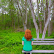 Lonely woman rear view looking to forest sitting on bench — Stock Photo