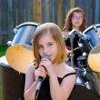 Blond kid girl singing in tha backyard with drums — Stock Photo #26187337
