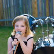 Blond kid girl singing in tha backyard with drums — Stock Photo