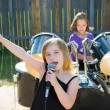 Stock Photo: Chidren singer girl singing playing live band in backyard