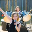 Chidren singer girl singing playing live band in backyard - Stock Photo