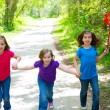 Friends and sister girls running in the forest track happy — Stock Photo