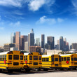 School bus in a row at LA skyline photo mount — Stock Photo
