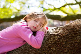 Blond children kid girl having a nap lying on a tree — Stock Photo