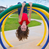 Children kid girl upside down on a park ring — Stock Photo