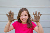 Happy kid girl playing with mud with dirty hands smiling — Stock Photo