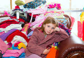 Blond kid girl sitting on a messy clothes sofa — Stok fotoğraf