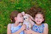 Twin sisters playing with chihuahua dog lying on lawn — Stock Photo