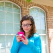 Teenager girl with glasses playing with smartphone — Stock Photo #26190035