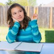 American latin teen girl doing homework on backyard — Stock Photo #26190259