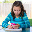 Teen girl with smartphone doing homework — Stock Photo #26190319