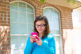 Teenager girl with glasses playing with smartphone — Stock Photo