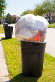 Trash bin dustbin full of garbage on street lawn — Stock Photo