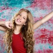 Blond happy kid girl in red happy with arms up — Stock Photo