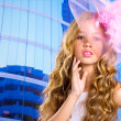 Blond fashion girl with pink hat in blue skyscrapers — Stock Photo