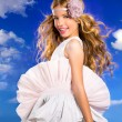 Blond girl with fashion dress blowing hair in blue sky — Stock Photo #28275231