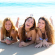 Stock Photo: Happy three friends girls lying on beach sand smiling