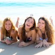 Happy three friends girls lying on beach sand smiling — Stock Photo