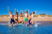 Happy excited teen boys and girls beach jumping — Stock Photo