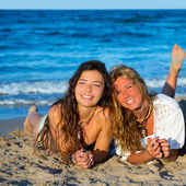 Girls friends having fun happy lying on the beach — Stok fotoğraf