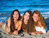Girls friends having fun happy lying on the beach — Stock Photo