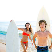 Surfers boy and teen girl with surfboard in beach — Stock Photo