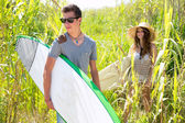 Surfer boy and girl walking in the green jungle — Stock Photo